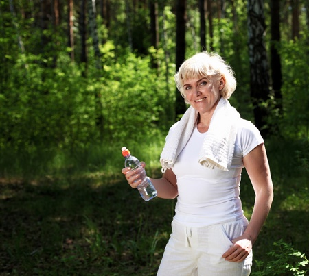 55 years old: An elderly woman after exercising in the forest holding a bottle of water