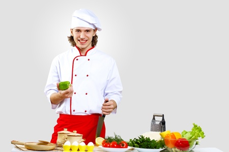 Portrait of a young cook in uniform preparing meal Stock Photo - 13220424