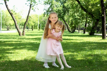 Two little sisters together in the summer park Stock Photo - 13226674