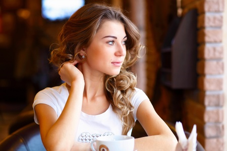 Portrait of young pretty woman sitting in restaurant photo