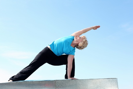 Portrait of a senior woman doing yoga outdoors photo