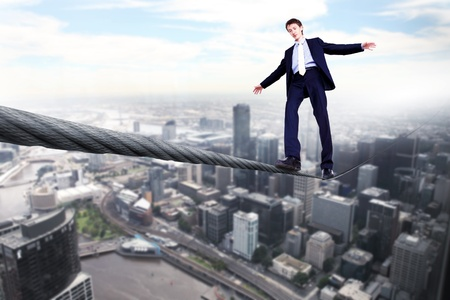 inconstant: Business man balancing on the rope high in the sky Stock Photo
