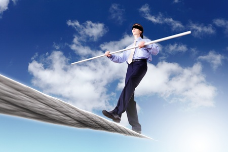 even: Business man balancing on the rope high in the sky Stock Photo