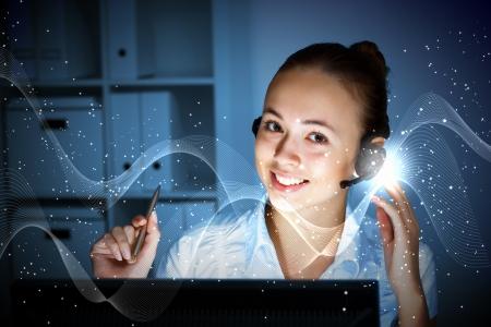 Giovane donna in abbigliamento d'affari in cuffia lavorare con il computer Archivio Fotografico
