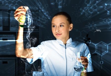 examenes de laboratorio: Químico joven en uniforme blanco que trabaja en el laboratorio de