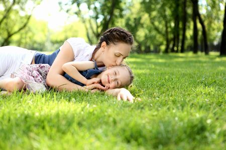 Mother with her daughter outside in the summer park photo