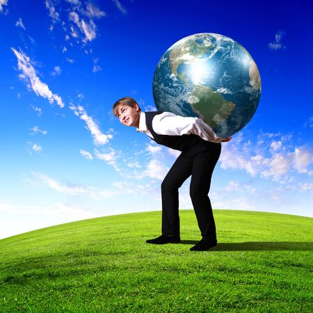 Young businessman carrying world on his back photo