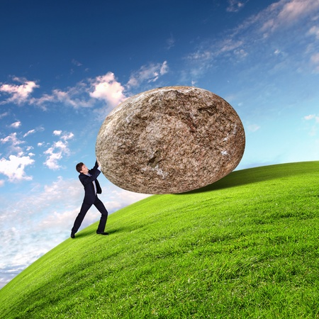 difficulties: Image of businessman rolling a giant stone Stock Photo