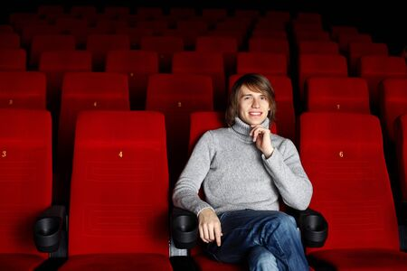 Young man in grey sweater sitting in the cinema alone photo