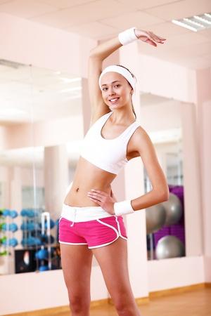 aerobica: Giovane donna in abbigliamento sportivo fare sport in palestra