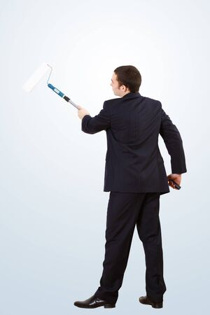 Young businessman standing against blank wall with brush photo
