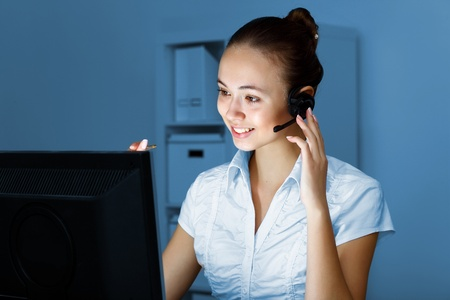 Young woman in business wear in headset working with computer photo