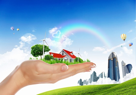 house in hand: Human hand holding houses surrounded by nature against blue sky and rainbow Stock Photo