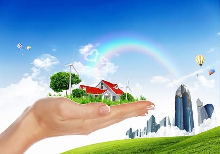 Menschliche Hand, die Häuser von Natur aus gegen den blauen Himmel und Regenbogen umgeben