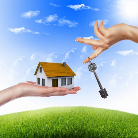 Human hand against blue sky background and house Stock Photo