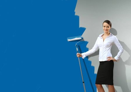 Young businesswoman with a paint brush against blue wall photo