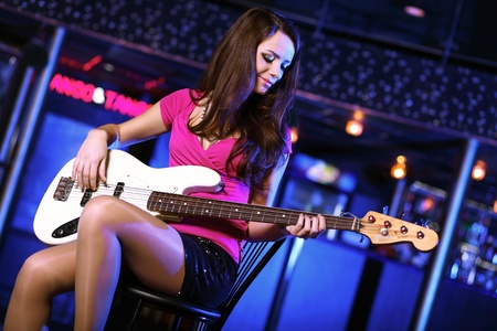 Young guitar player with instrument performing in night club photo