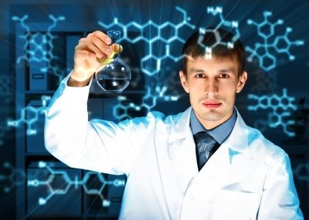 Joven químico con el uniforme blanco de trabajo en el laboratorio Foto de archivo