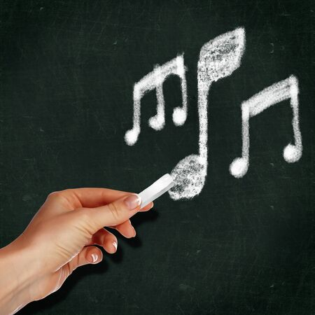 School blackboard and hand with chalk writing musical notes on it photo
