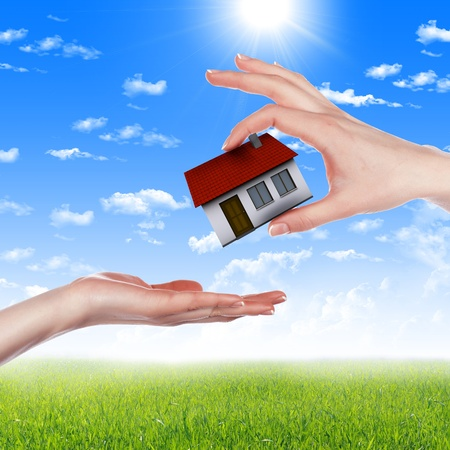 human hands holding model of a house against nature background photo