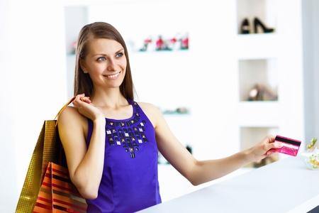 compras compulsivas: Joven y bella mujer haciendo compras con tarjeta de cr�dito Foto de archivo