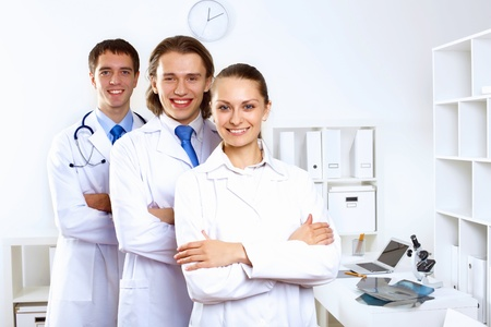 Group of doctors in uniforms together in clinic photo