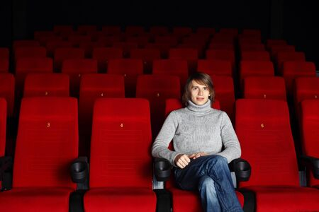 Young man sitting in cinema and watching movie Stock Photo - 13302983