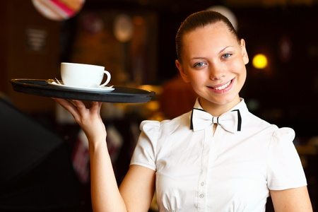 20s waitress: Portrait of young waitress in white blouse holding a tray