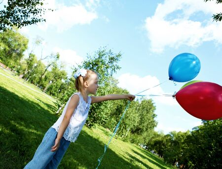 Portrait of a little girl playing in green summer park with balloons photo