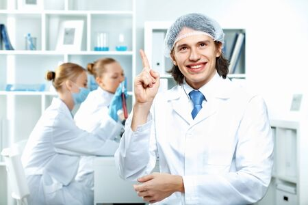 Young scientists in white uniform working in laboratory Stock Photo - 13307494