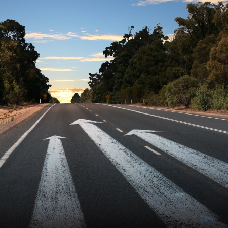 forward: Empty countryside road with white arrow sing on it Stock Photo