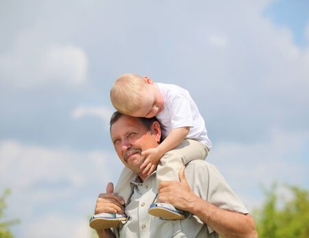 little boy sitting on the shoulders of his grandfather photo