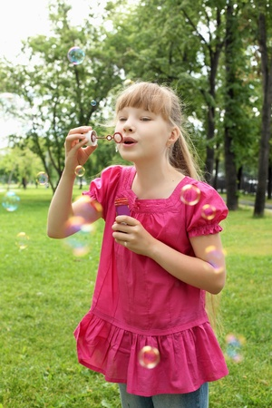 Little girl in the summer park blowing bubbles photo
