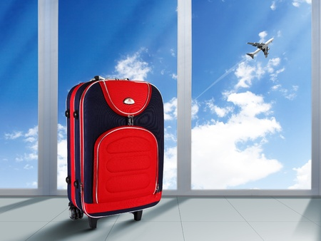 Red suitcase and plane in the blue sky above photo