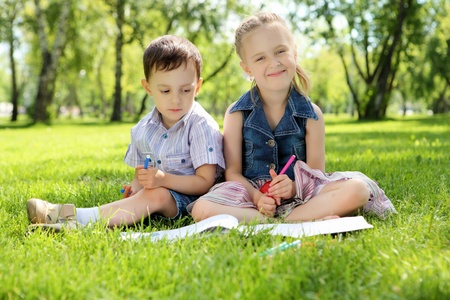 Sister and brother in the park reading a book photo