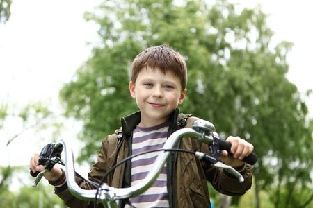 Happy smiling boy on a bicycle in the green park Stock Photo