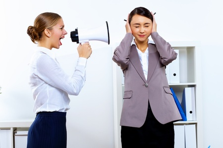 Young woman in business wear with megaphone in office photo