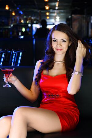 Portrait of young attractive woman in night club with a drink photo