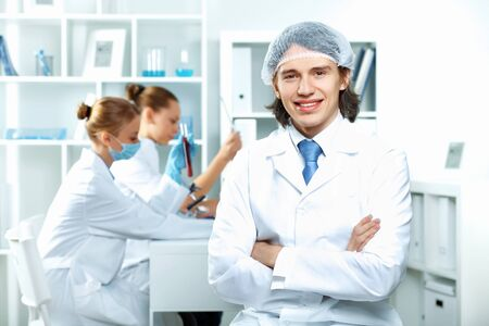Young scientists in white uniform working in laboratory photo