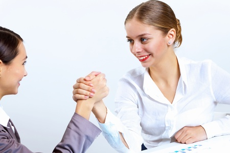 Two young women in business wear arm wrestling in office photo