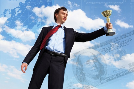 young businessman in a suit with a golden cup against blue sky photo