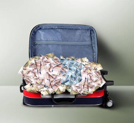 Picture of red travel suitcase full of banknotes photo