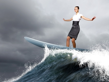 Image of a busineswoman surfing on the sea waves photo