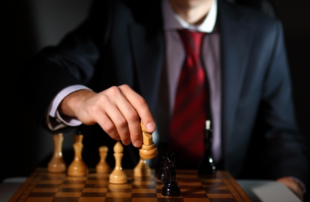 chess men: Image of a businessman in dark suit playing chess
