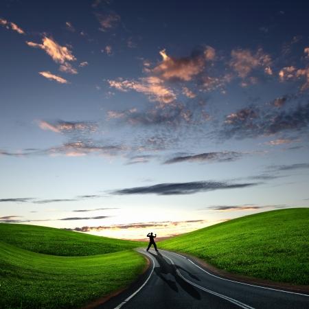 hombre solo: Collage con una figura humana alejándose por la carretera coubtry Foto de archivo