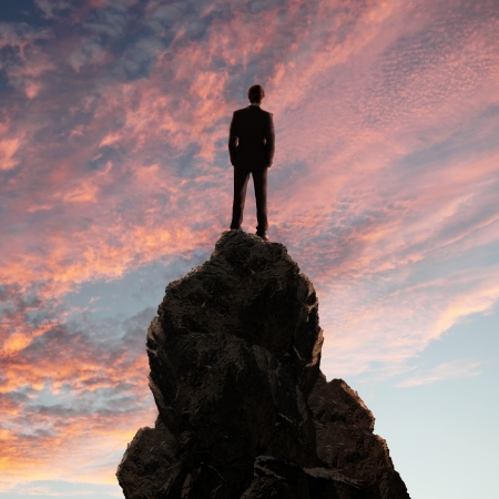 Image of a businessman standing on the top of a high mountain