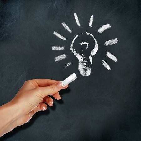 School blackboard and human hand drawing light bulb symbol photo