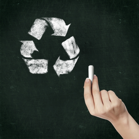 School blackboard and hand with chalk drawing recycle symbol photo