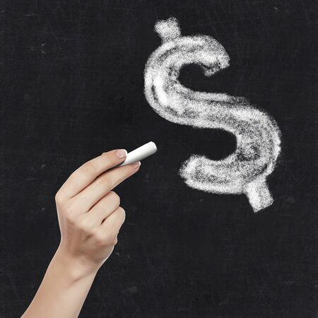 School blackboard and hand with chalkdollar symbol writing on it photo