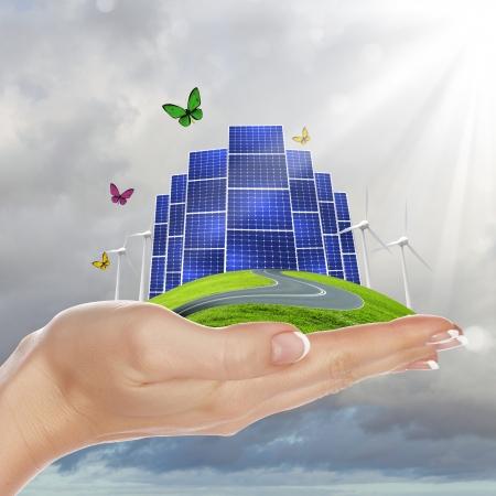 sustentabilidad: Manos que sostienen una tierra verde con batareis solares Foto de archivo